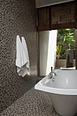 Free-standing bathtub and mosaic tiles on walls and floor in modern bathroom with open doorway leading to courtyard
