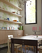Dining table with chairs in front of open shelving and a sideboard in a wall niche