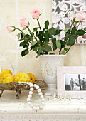 Dish of lemons next to roses in white vase