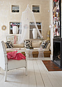 Armchair with white leather upholstery and sofa made of bamboo poles in modern country house