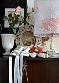 Ladies' shoes next to vase of flowers and table lamp with fabric lampshade