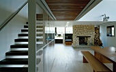 Open-plan living space with dining table, fireplace and staircase separated by glass wall