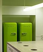 Zwei grüne Kühlschränke in einer Büro-Küche