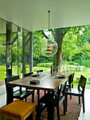 Elegant table and chairs in dark wood and Bauhaus pendant lamp on terrace with view of garden