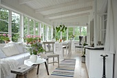 Spacious veranda with comfortable bench and rustic side table next to dining area in white wooden house