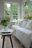 Bench covered with white lace throw and rustic side table in corner of loggia with view of garden