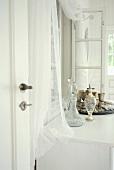 Antike Karaffen aus Kristallglas auf weißem Sideboard vor Wand mit Fenster in ländlichem Ambiente