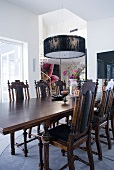 Elegant dining table and chairs in antique English style below modern pendant lamp