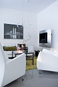 A modern seating area with white designer furniture and a stainless steel fireplace