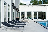 Black aluminium loungers on a concrete terrace by a swimming pool