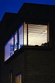 Contemporary house at night with lit window