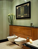 Wall-hung bidet and toilet on half-height wood-panelled wall in bathroom