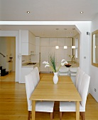 Wooden dining table and chairs with white upholstery in open-plan living space