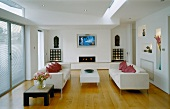 Elegant living room with white sofas on wooden floorboards