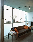 Wall lamp on swivelling cantilever arm and black leather couch in front of opaque glass wall in contemporary living space