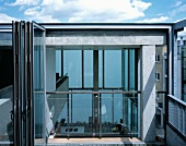 Roof terrace with open folding glass door and view of gallery and interior