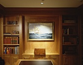 Wood-panelled wall with illuminated picture in niche and integrated shelves