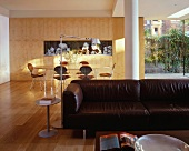 Black leather couch and dining area in modern, open-plan living space