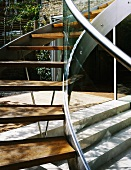 Curved staircase in courtyard with stainless steel stringer and wooden treads