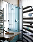 Small designer bathroom with washstand next to glass shower partition and stainless steel, heated towel rail