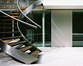 Curved staircase with stainless steel stringer and wooden treads in courtyard of contemporary house