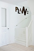 White staircase with safety gate and large letters on wall
