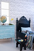 Black bed next to pale blue chest of drawers in child's bedroom