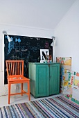 Rag rug, orange wooden chair and green cabinet in front of blackboard on wall