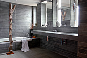 A grey bathroom with stone tiles on the floor and on the walls with a tall wooden sculpture in front of a bathtub