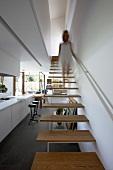 Eine Frau steigt deine minimalistische Treppe hinab in den offenen Wohnbereich mit Schieferboden und verglaster Terrassanfront