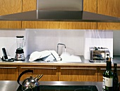 Extractor hood in front of modern, wooden fitted kitchen