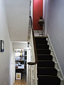 Black runner on white wooden stairs in modernised house