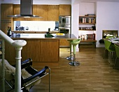 Open-plan kitchen with island and designer bar stools with green shell seats