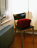Metal chair with black leather upholstery on seat and back next to radiator painted silver-grey