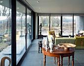 Antiker Beistelltisch mit Antiquitäten im Wohnraum mit raumhohen Terrassenfenstern