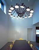 Retro pendant lamp with cantilever arms above dining table in minimalist room