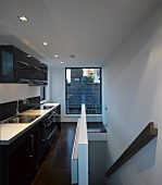 Modern kitchen with stairs and window overlooking neighbouring roof