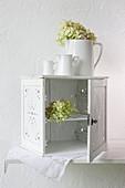 Weisses Holzschränkchen mit offenen Türen und mehrteiligen Krügen mit Blumen