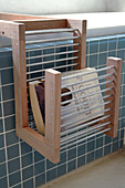 Rack made of wood and metal rods on blue-tiled bathtub