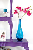 Orchids in blue glass vase on stacked, halved, antique-style tables painted purple