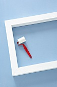 White-painted wooden frame and small paint roller on pastel blue background