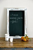 Blackboard with shopping list standing on rustic table leaning on wall