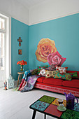 Mediterranean living room with sofa and colourful cushions against wall painted light blue with large floral motif