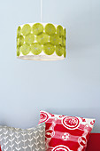 Pendant lamp with retro-patterned shade above colourful cushions