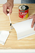 Painting the edge of a white plastic container with glue