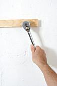 Screwing screws into wall