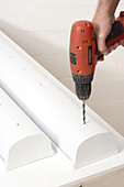 Drilling holes in white plastic container