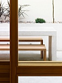 View of terrace with table and benches through window