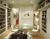 Zimmer mit rundem Glastisch und eingebauten Bücherregalen