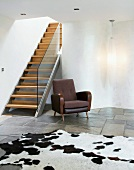 Contemporary staircase in purist living space with cow skin rug on stone floor